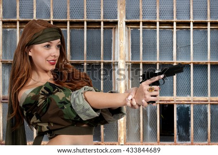 Gun toting beautiful young woman soldier with a pistol - stock photo