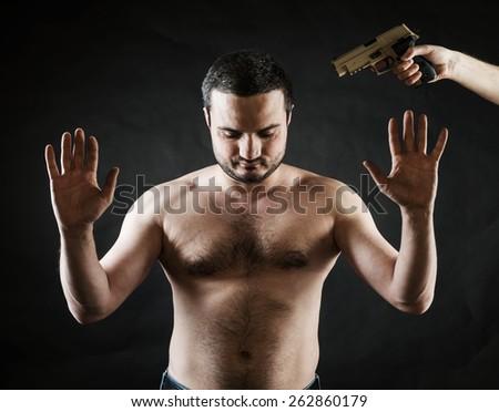gun was set to head hostage on a black background - stock photo