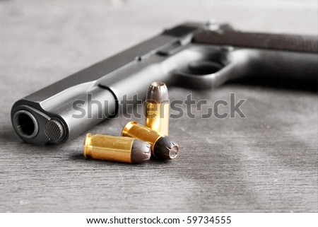 Gun with bullets. Gun is desaturated for stronger effect on bullets - stock photo