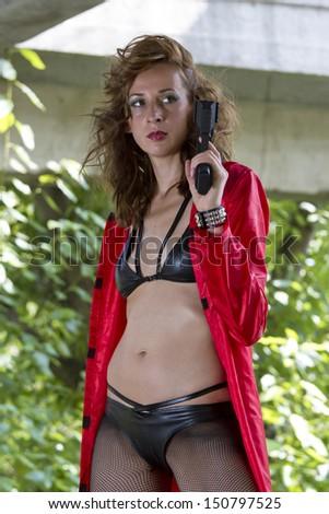 Gun woman in leather bikini and red coat posing outdoor - stock photo