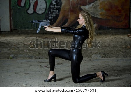 Gun woman in leather catsuit shooting from machine gun - stock photo