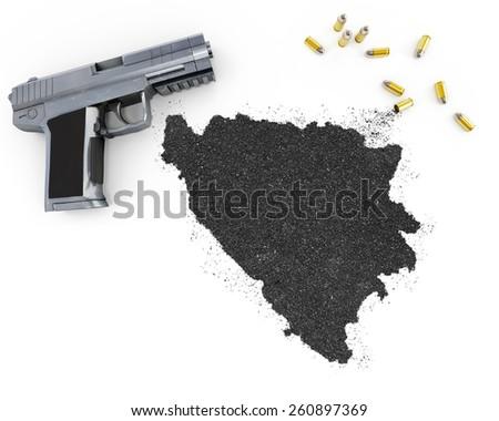 Gunpowder forming the shape of Bosnia and Herzegovina and a handgun.(series) - stock photo