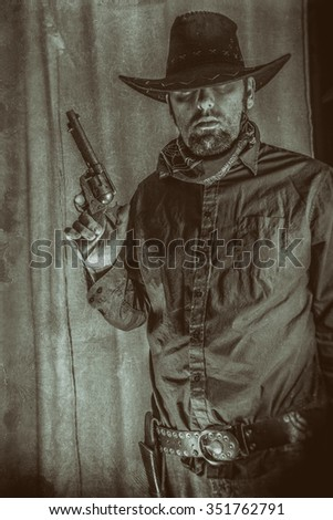 Gunslinger Cowboy Holding up Gun. Cowboy cautiously holds up colt 45 gun. Edited with a vintage film effect. - stock photo