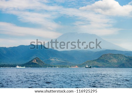 Gunung Agung the highest volcano on Bali island, Indonesia with blue cloudy sky and big ships on the sea on front. - stock photo