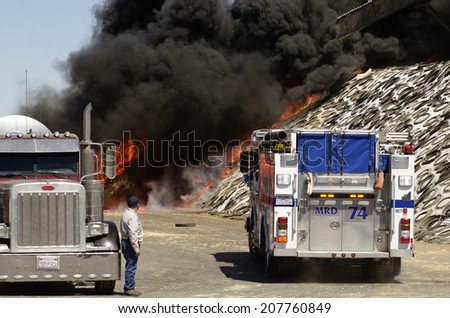 GUSTINE, CA, USA - JUNE 18, 2014: Fire fighters respond to a semi truck and silage fire at a dairy farm in Gustine, CA, on June 18, 2014