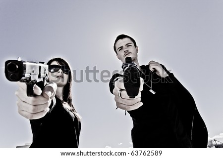 Guy and a girl pointing two guns - stock photo