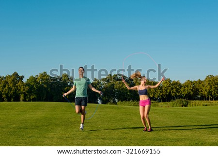 Guy and girl are jumping on the jump rope. Physical education on a green meadow. Young sportsmen do warm-up on a golf course. Sports on the street.