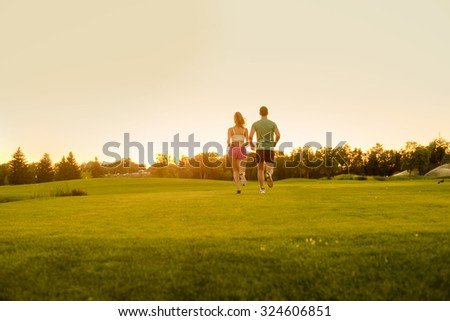 Guy and girl running on the green zone. Clean environment. Healthy lifestyle. Sports jogging outdoors. Running athlete. - stock photo