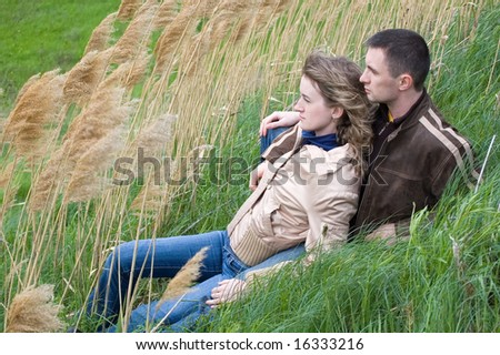 guy and girl sits in canes and look forward - stock photo