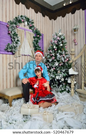 Guy and girl with a gift near a fir-tree
