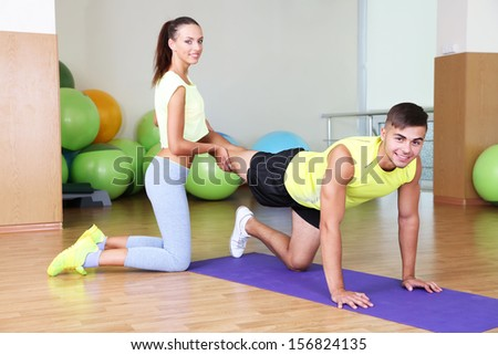 Guy and trainer engaged in fitness room