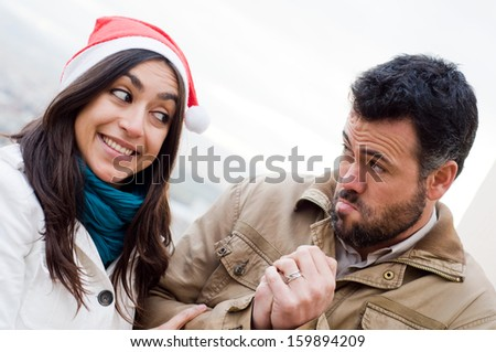guy asks a gift to girl with santa claus cap - stock photo