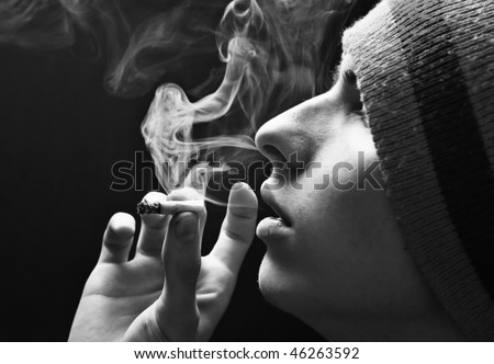 Guy blows smoke on a dark background - stock photo
