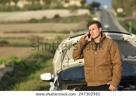 Guy calling roadside assistance for his breakdown car i a country road - stock photo