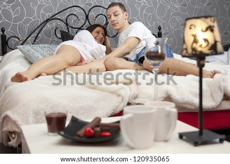 guy caresses his girlfriend in bed in the morning - stock photo