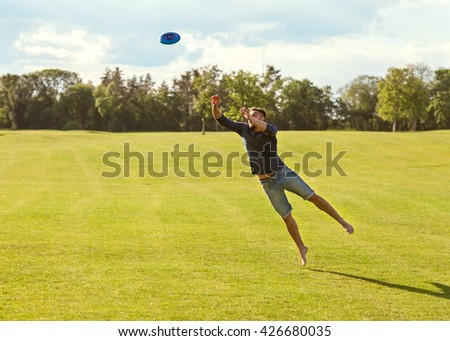 guy catches a disk in a jump on a green field - stock photo