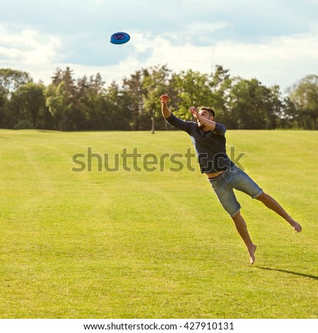guy catches a frisbee in a jump on a green field - stock photo