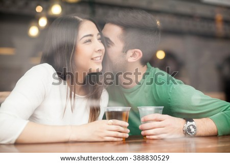 Guy drinking beer at a bar and whispering something in a woman's ear - stock photo
