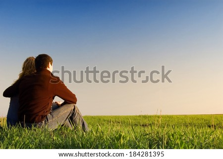 guy embraces girl on a spring field - stock photo