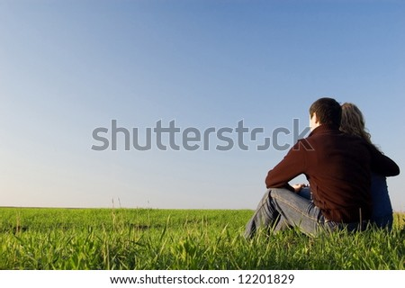 guy embraces girl on a spring field. Low foreshortening - stock photo