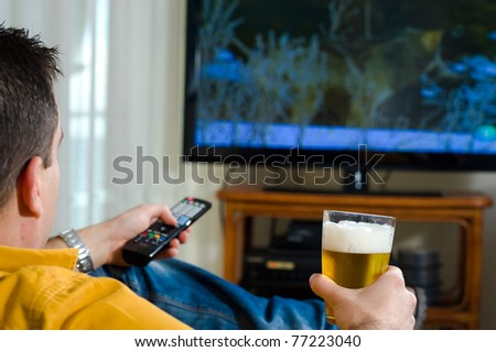 Guy enjoying his evening beer in front of the television - stock photo