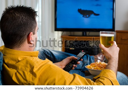 Guy enjoying his evening watching television from the sofa - stock photo