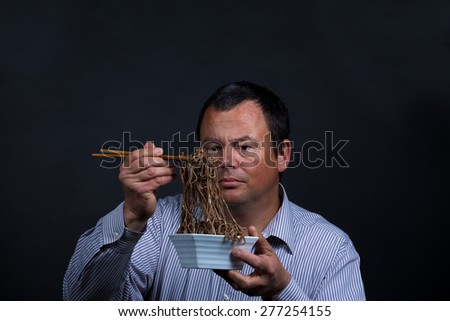 Guy experiencing how difficult it can be to eat with chopsticks - stock photo
