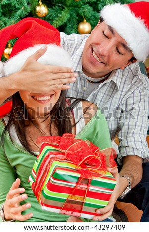 guy giving a surprise to his girlfriend on christmas - stock photo