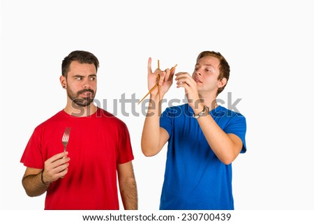 Guy having trouble holding chopsticks, his friend being pretty amused - stock photo