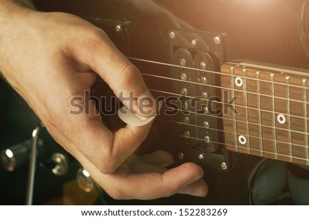 guy holding a guitar pick - stock photo