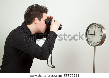 Guy holding binoculars and looking at the clock - stock photo