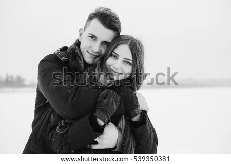 guy hugging his girlfriend from behind in the park, in winter holidays