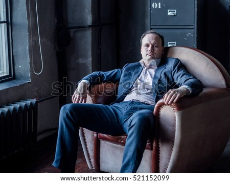 guy in a suit sitting on a background of steel file cabinets, wardrobe in the room by the window