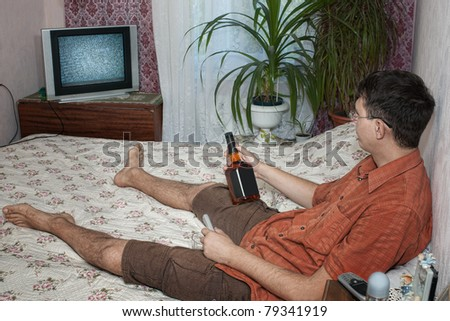 Guy in bed with bottle of whiskey watching tv