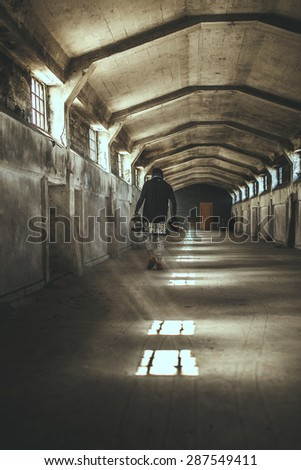 Guy in gangster clothing and face mask in catacombs - stock photo