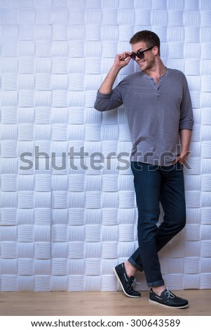 Guy in grey long-sleeve shirt is standing at the white wall and giving a smile.