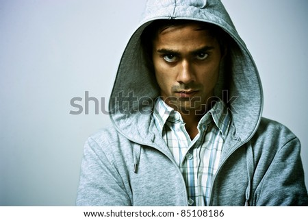 Guy in hood with tough expression - stock photo