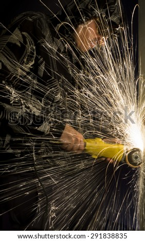 Guy in protective goggles drills metal grinder and sparks jump out everywhere - stock photo