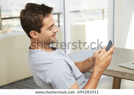 Guy in shirt texting on Smartphone, smiling
