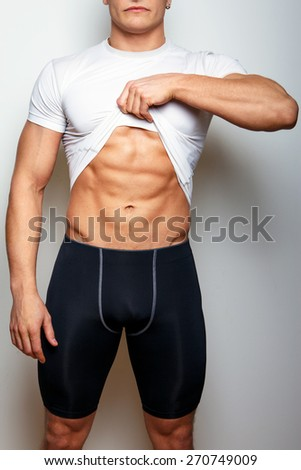 Guy in spoertswear showing his muscular stomach