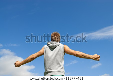 Guy in sports clothing, with his arms spread, looking at blue sky.