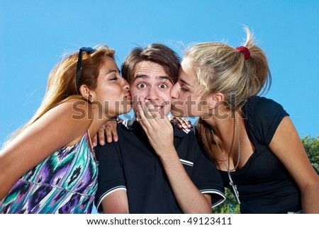 guy kissed by two attractive girls - stock photo