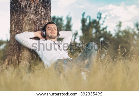 Guy listen music - enjoy - repose in grass. Man leaning against a tree relaxing - resting. Outdoors - outside - stock photo