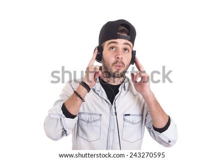 Guy listening and enjoying music using headphones and wearing black cap - stock photo