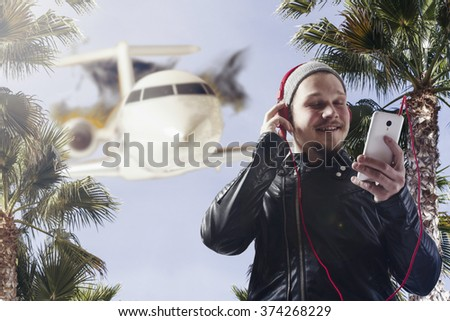 Guy listening to music with plane behind - stock photo