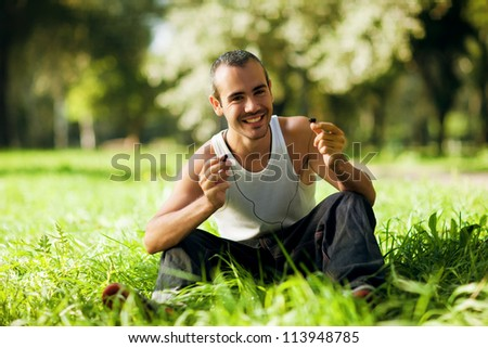 guy listening to the player sitting on the grass - stock photo