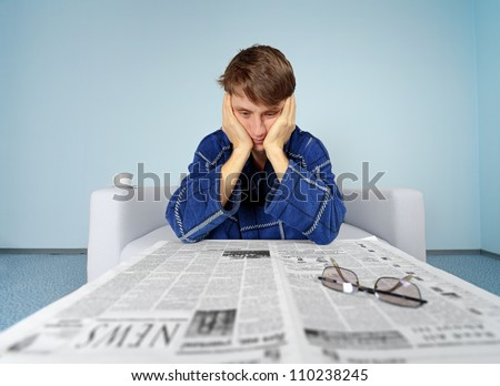 Guy looking a job at home. Bad news from newspaper - no work - stock photo