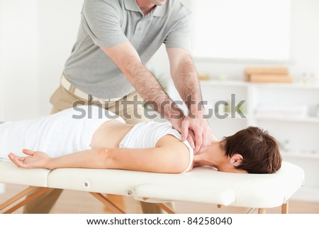 Guy massaging a cute woman's neck in a room