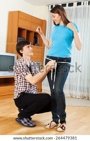 Guy measuring  butt of girlfriend with measuring tape at home  - stock photo