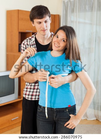 Guy measuring smiling girlfriend with measuring tape - stock photo